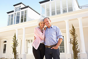Mature couple standing in front of large home with many windows.